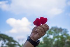 Het rode hart wordt gehouden voor de blauwe hemel en is lichtjes bewolkte en exemplaarruimte de Dag van conceptenvalentine ` s royalty-vrije stock foto