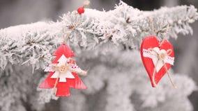 Het rode houten het hart en de sparren hangen van het Kerstmisspeelgoed op de takken van de snowly Kerstboom videomotie hd stock videobeelden