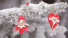 Het rode houten het hart en de sparren hangen van het Kerstmisspeelgoed op de takken van de snowly Kerstboom videomotie hd stock video