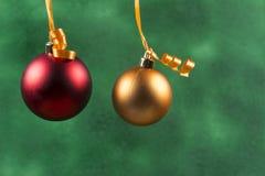 het rode Kerstmisbal hangen met oranje lint op groene achtergrond stock afbeeldingen