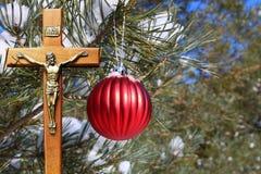Het rode Kerstmisdecoratie hangen van openluchtboom met kruisbeeld stock fotografie