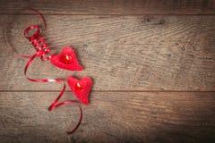 Het rode lint, kaarsen in de vorm van hart op een donkere houten lijst De achtergrond van de valentijnskaartendag, rustieke stijl Royalty-vrije Stock Afbeeldingen