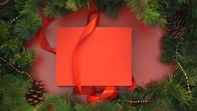 Het rode lint losknopen en giftbox met houten Kerstmisspeelgoed die, decoratie openen