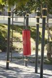 Het rode ponsenzak hangen op de bar in de zomerpark Stock Foto's