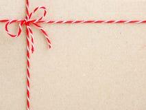 Het rode strengkoord bond een boog op document achtergrond vast stock afbeeldingen