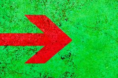 Het rode teken van de pijlrichting over de levendige heldergroene muur van de kleurensteen met onvolmaaktheden en barsten stock afbeelding