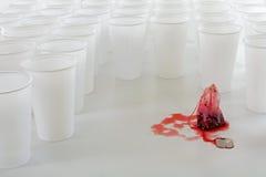 Het rode theezakje bezet door een groep witte plastic koppen, vat conc samen Stock Afbeeldingen