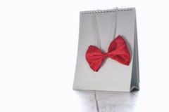 Het rode vlinderdas hangen op lege kalender op witte achtergrond Royalty-vrije Stock Afbeeldingen