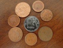 Het roebelmuntstuk wordt omringd door Euro muntstukken op een bruine houten achtergrond stock fotografie