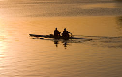 Het roeien bij zonsopgang Stock Afbeelding