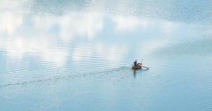 Het roeien kruis een blauwe rivier in moerasland Royalty-vrije Stock Afbeelding