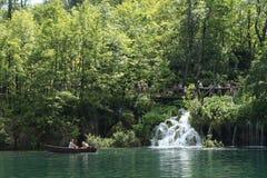 Het roeien van boot in één van de meren en de mensen die van Plitvice op een weg lopen Stock Afbeeldingen