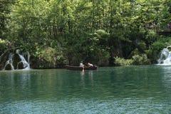 Het roeien van boot in één van de meren en de mensen die van Plitvice op een weg lopen Royalty-vrije Stock Fotografie