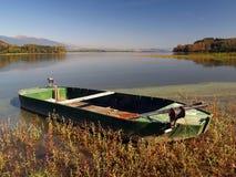 Het roeien van boot door meer Stock Afbeelding