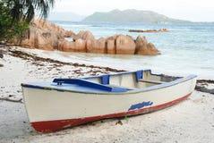 Het roeien van Boot op Tropische Oever stock afbeeldingen