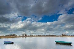 Het roeien van boten die op een klein meer drijven. stock afbeeldingen