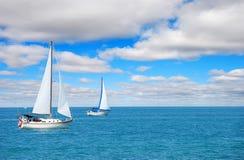 Het roeien van het zeil op blauw water Stock Foto
