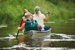 Het roeien van mensen op rivier Stock Afbeeldingen