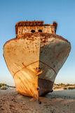 Het roestige schip is op het zand oezbekistan Stock Afbeelding