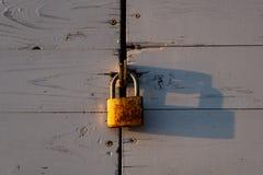 Het roestige slot hangen op een houten deur stock afbeeldingen