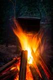 Het roetige pottentoerist hangen over de brand Royalty-vrije Stock Fotografie