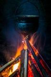 Het roetige pottentoerist hangen over de brand Royalty-vrije Stock Afbeeldingen