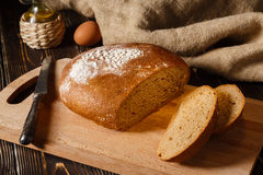 Het roggebrood ligt op een broodplank Stock Foto