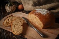 Het roggebrood ligt op een broodplank Stock Afbeeldingen
