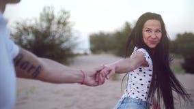 Het Romaanse Concept, Jong Paar, Holdingshanden loopt blootvoets op zand, vrouw die de hand van haar minnaar, looppas vooruit hou stock video