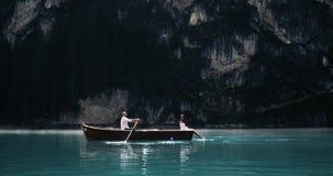 Het romantische aantrekkelijke paar in het midden van het meer, met een houten boot de man roeit en zijn meisje is stock videobeelden