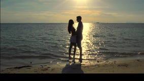 Het romantische Coulpe-Kussen op het Strand bij Zonsondergang stock footage
