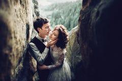 Het romantische jonggehuwdepaar stellen in zonsonderganglichten op majestueuze roc stock fotografie