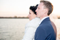 Het romantische landschap, jonggehuwdepaar het stellen bij zonsondergang dichtbij de rivier, de bruidegom houdt de hand van een b stock foto's
