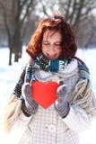 Het romantische meisje dat van de winter een hart in openlucht houdt Stock Afbeeldingen