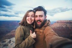 Het romantische paar of de vrienden tonen duimen en maken selfie foto op reis wandelend in Grand Canyon in Arizona Stock Foto's