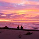 Het romantische paar geniet van spectaculaire strandzonsondergang Royalty-vrije Stock Foto's