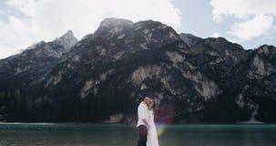 Het romantische paar koestert gelukkig elkaar, is de achtergrond een grote berg Langzame Motie stock footage
