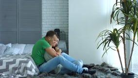 Het romantische paar in liefde omhelst zitting op vloer stock footage