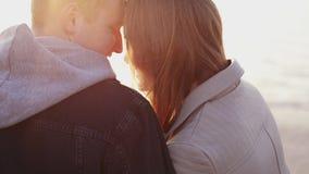 Het romantische paar ontspannen bij avond, het verblinden van zon, meer, het strelen stock footage