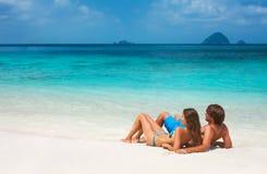 Het romantische paar ontspannen op het strand stock afbeeldingen