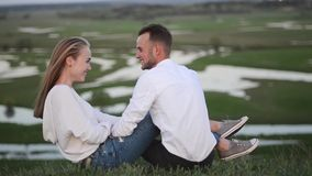 Het romantische paar zit en koestert op mooi aardgebied stock videobeelden