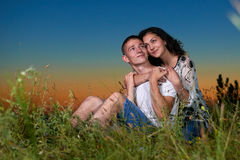 Het romantische paar zit op gras bij zonsondergang op openlucht, mooi landschap en de donkere hemel van de nachthemel, het concep Royalty-vrije Stock Foto