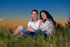 Het romantische paar zit op gras bij zonsondergang op openlucht, mooi landschap en de donkere hemel van de nachthemel, het concep Stock Fotografie