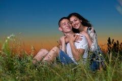 Het romantische paar zit op gras bij zonsondergang op openlucht, mooi landschap en de donkere hemel van de nachthemel, liefdeconc Stock Foto