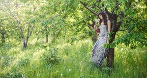 Het romantische vrouw stellen op groene achtergrond royalty-vrije stock foto