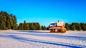 Het rood dilapidated en verliet huis op een breed sneeuw behandeld gebied in Glen Valley in Fraser Valley van Brits Colombia royalty-vrije stock fotografie