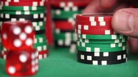 Het rood dobbelen en de casinospaanders in vingers op groene lijst stock video