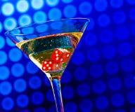 Het rood dobbelt in het cocktailglas op blauwe bokeh Stock Afbeelding