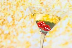 Het rood dobbelt in het cocktailglas op gouden Stock Fotografie