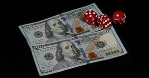 Het rood dobbelt het rollen op Dollarrekeningen tegen Zwarte Achtergrond, stock footage